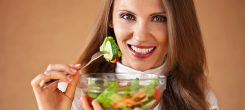 happy healthy woman eating salad, close up