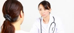 japanese female doctor talks by serious expression with patient